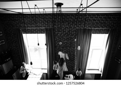 Woman takes a wedding dress hanging on the brick wall in an industrial loft apartment