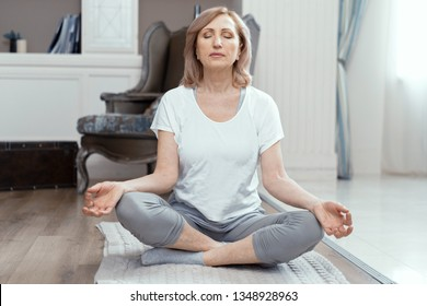 A Woman Takes Yoga at Home. Woman Over 50 Years Old. She Took the Pose of the Asana on the Floor. Closing Her Eyes She Meditates. Close Up Shot.