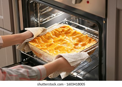 Woman taking of baking dish with prepared lasagna out of oven