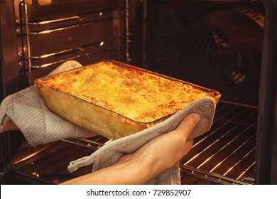 Woman taking baking tray with spinach lasagna out of oven