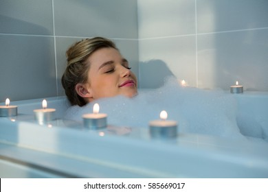 Woman taking bath in bathtub at bathroom
