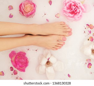 Woman is taking bath. Close up of female feet and hands in bath full of water and flowers.