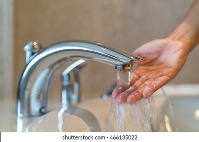 Woman taking a bath at home checking temperature touching running water with hand. Closeup on fingers under hot water out of a faucet of a sink or bathtub in house bathroom