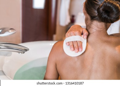 Woman taking a bath at luxury hotel scrubbing back skin with hand scrub sponge removing dead skin cells for body, skincare exfoliation. People skin care lifestyle.