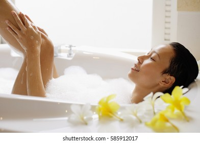 Woman taking a bath, washing leg