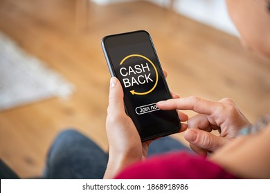 Woman taking benefit of cash back using smart phone, shopping and money refund concept. Close up hand holding smartphone with button to get started the cashback.  - Shutterstock ID 1868918986