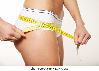 Woman taking body measurements around the hips.