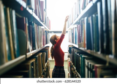 Woman taking book from library bookshelf. Librarian searching books