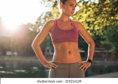 Woman taking break after sports training. She is standing with her hands on hips looking down on a summer day. Female athlete in wearing a smartwatch.