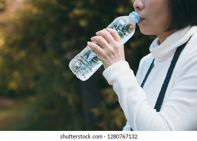 woman taking a break to drink from water bottle while walk traveling