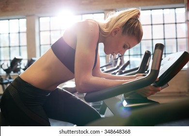 Woman taking break during cycling workout in gym. Female on gym bike doing cardio exercise.