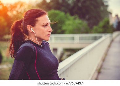 Woman taking a break from training and listening the music