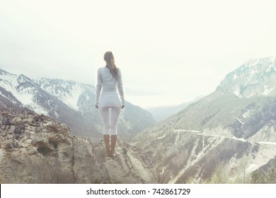 woman taking a breath on the top of a mountain