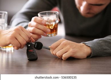 Woman taking car key from drunk man in bar, closeup. Don't drink and drive concept