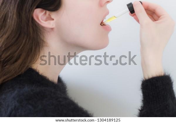 Frauen, die CBD-Öl unter der Zunge aufnehmen