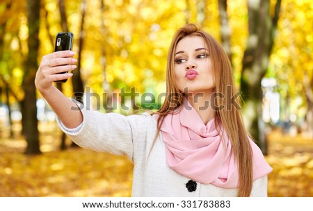 woman taking duckface selfie portrait in autumn city park