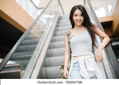 Woman taking escalator in shopping mall
