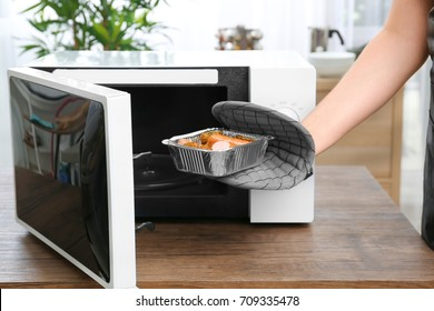 Woman taking foil baking tin with potato and sausages out from microwave in kitchen