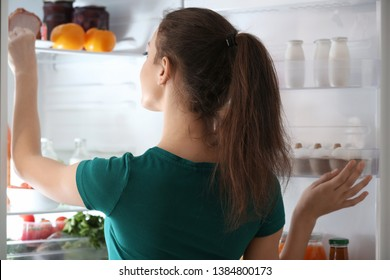 Woman taking food out of fridge at home