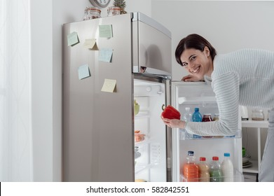 Woman taking a fresh healthy pepper from the fridge and smiling at camera