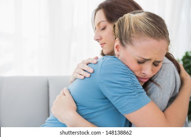 Woman taking her friend in her arms and sitting on the sofa