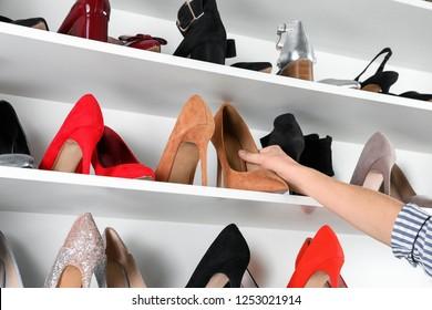 Woman taking high-heeled shoe from shelving unit, closeup