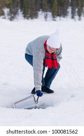 Woman taking a household water from a ice hole.