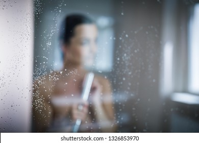 Woman taking a long hot shower washing her hair in a modern design bathroom