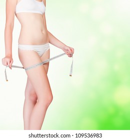 Woman taking measurements of her body on blurry background with copyspace.