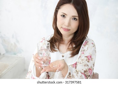 woman taking medication holding a glass of water in one hand as she slips a tablet or antibiotic