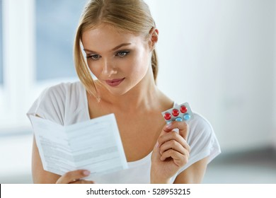 Woman Taking Medicine. Beautiful Young Female Holding Blister Pack With Pills In Hand And Reading Medical Instructions. Attractive Girl Looking At Instruction, Holding Pill Package. High Resolution