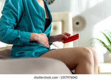 Woman taking the medicine and pills because of painful stomach ache. Person suffering from abdominal pain due to menstruation and PMS. Inflammation and infection, cystitis. Drug treatment and therapy