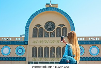 Woman taking mobile photo of the Central Souq (market) in Sharjah City, United Arab Emirates