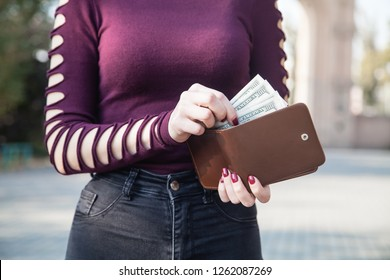 Woman taking money from her wallet.