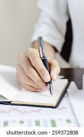 Woman taking note with a pen