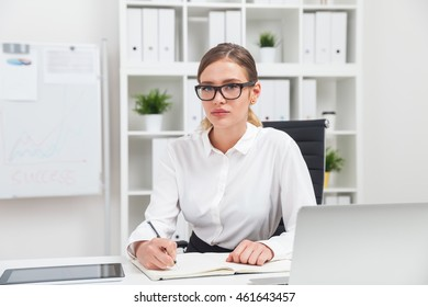 Woman taking notes Business lady in glasses and formal clothes sitting at her workplace writing in notebook and looking at camera.