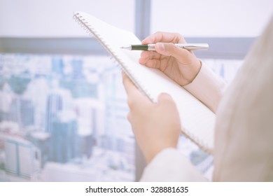 Woman taking notes during business meeting in the office.