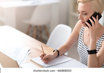 Woman taking notes and talking on smartphone