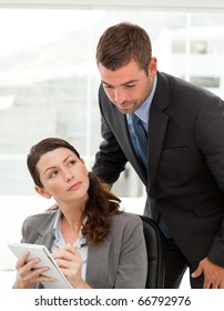 Woman taking notes while talking with her boss at her desk