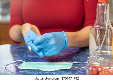 Woman is taking off disposable hygiene gloves from her hands closeup
