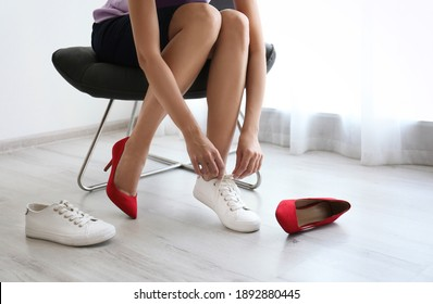 Woman taking off uncomfortable shoes and putting on sneakers in office, closeup. Tired feet after wearing high heels