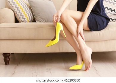 Woman taking off yellow high heels shoes.