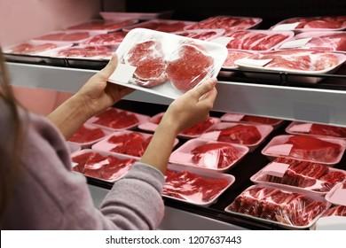 Woman taking packed pork meat from shelf in supermarket
