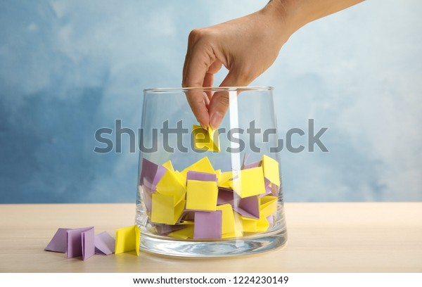 Woman taking paper piece from glass vase on table. Lottery