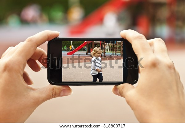 Woman taking a photo of baby girl with smartphone - POV shot