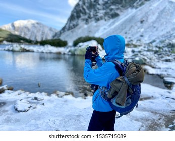 Woman taking photo of the blue clear mountain lake with snowy hill mountain peaks, Western Tatras mountains, Rohace Slovakia, autumn
