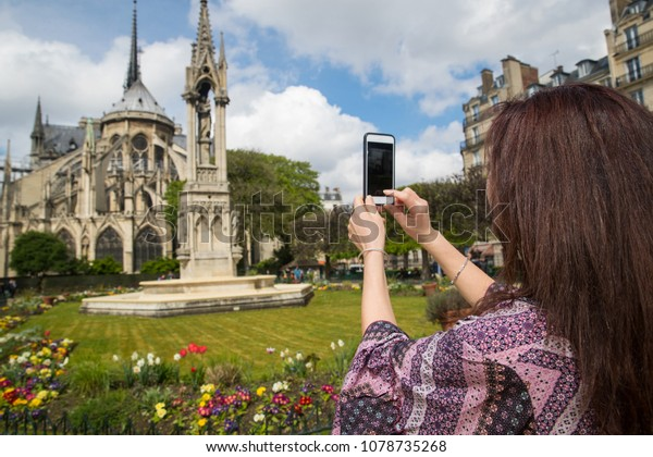 Woman taking photo with cell phone at Notre-Dame in Paris, Franc