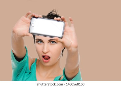Woman taking photo with cellphone. Isolated on background salmon shade red