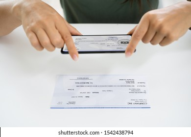 Woman Taking Photo Of Cheque To Make Remote Deposit In Bank