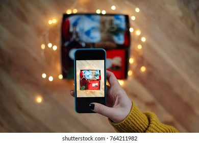 Woman taking photo of Christmas gift box with smartphone. Instagram photography blogging workshop concept. A girl hanging a phone taking a photo of present on wooden table